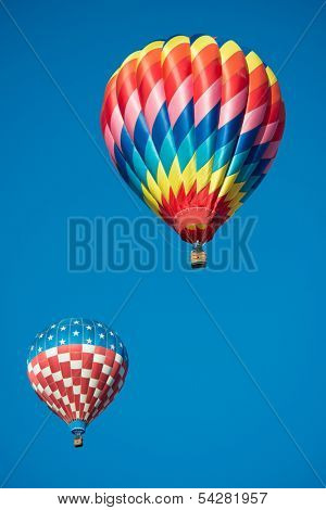 A Pair of brightly colored hot air balloons with a sky blue background
