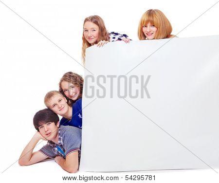 Teenagers hide behind a blank paper placard