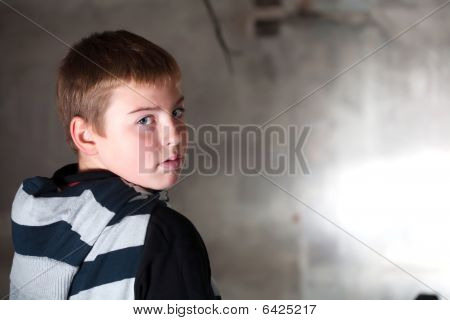 Boy Looking Over The Shoulder Against Grunge Background Lit With 3 Flashes