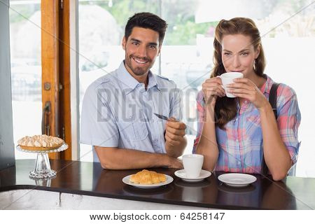Portrait of a smiling young couple with man holding credit card at the coffee shop