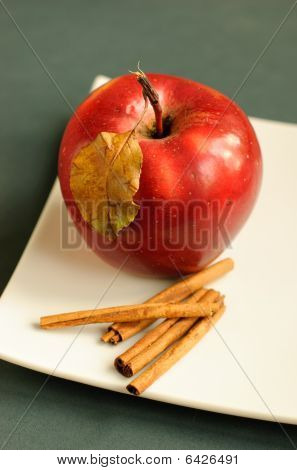 Apple with cinnamon and autumn leaves