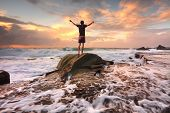 Teen boy stands on a rock among turbulent ocean seas and fast flowing water at sunrise. Worship praise zest adenture solitude finding peace among lifes turbulent times. Overcoming adversity. Motion in water poster