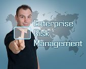 Young man press digital Enterprise Risk Management button on interface in front of him poster