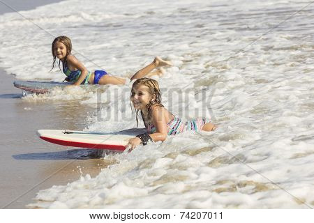 Cute little girls boogie boarding in the ocean waves
