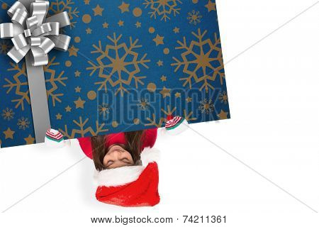 Festive little girl showing card against christmas wrapping paper with bow poster