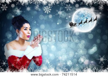 Pretty santa girl blowing over her hands against fir tree forest and snowflakes