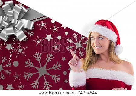 Festive blonde smiling and pointing against christmas wrapping paper with bow poster