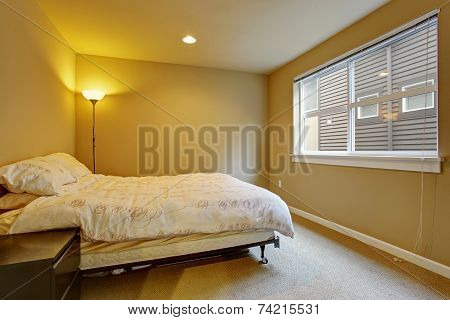 Warm Bedroom Interior With A Lamp Turned On