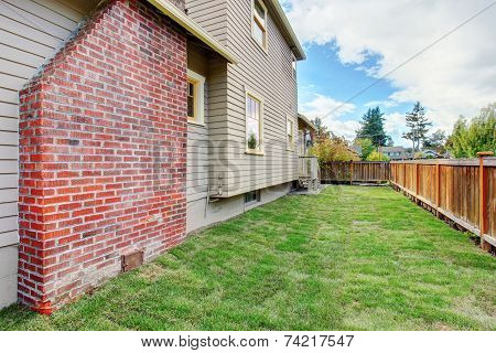 House With Brick Chimney And Fenced Backyard
