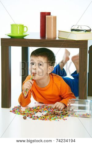 Happy kid eating lollipop under table sweets spilt. Home indoor, isolated on white.