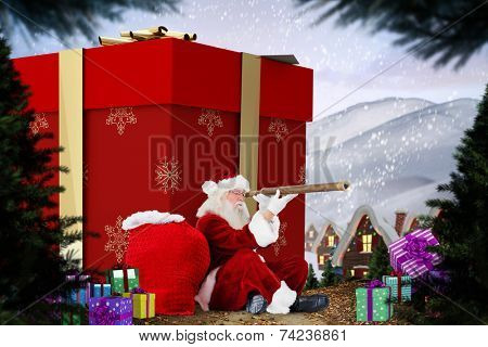 Santa looking through a telescope against cute village in the snow poster