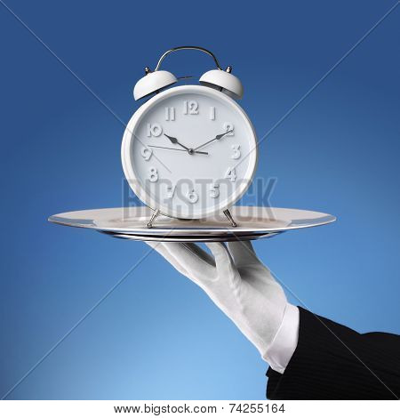 Waiter holding a silver platter with white alarm clock