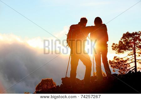 Hiking adventure healthy outdoors people standing talking. Couple enjoying sunset view above the clouds on trek. Video of young woman and man in nature wearing hiking backpacks and sticks.