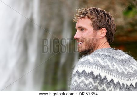 Handsome man in Icelandic sweater outdoor smiling by waterfall on Iceland. Portrait of good looking male model looking to side in nature.