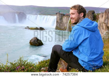 Iceland tourist relaxing by waterfall Godafoss. Man hiker resting on travel visiting tourist attractions and landmarks in Icelandic nature on Ring Road, Route 1.