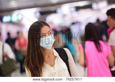 Person wearing protective mask against transmissible infectious diseases and as protection against pollution and the flu. Asian woman commuter in airport public area.