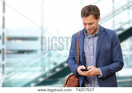 Young urban professional man using smart phone in office building indoors. Businessman holding mobile smartphone using app texting sms message wearing suit jacket and bag.