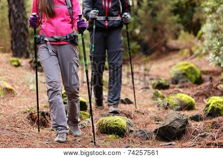 Hiking - Hikers walking in forest with poles on path in mountains. Close up of hiker shoes boots and hiking sticks poles. Man and woman hiking together. poster