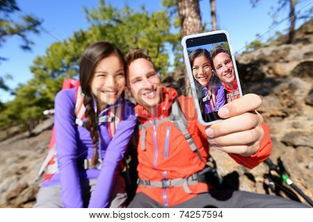 Selfie couple using smart phone hiking in nature with smartphone. Happy couple taking self-portrait photo picture using app. Man and woman having fun together. Focus on screen.