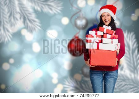 Woman holding many christmas presents against baubles hanging over christmas scene poster