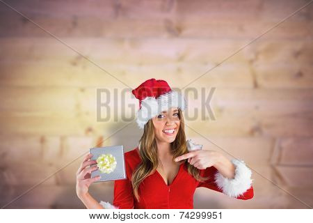 Sexy santa girl holding gift against blurred wooden planks poster