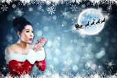 Pretty santa girl blowing over her hands against fir tree forest and snowflakes poster