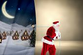 Santa claus pulling rope against grey room poster