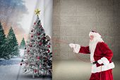 Santa pulls something with a rope against grey room poster