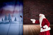 Santa pulls something with a rope against room with brick wall poster