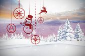 Hanging red christmas decorations against snowy landscape with fir trees poster