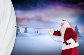 Santa pulls something with a rope against snowy landscape with fir trees poster