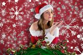 Sexy santa girl blowing over hands against snowflake wallpaper pattern poster