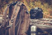 Lifestyle hiking camping equipment retro photo camera backpack and thermos outdoor forest nature on background poster