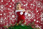 Pretty girl presenting in santa outfit against snowflake wallpaper pattern poster