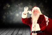 Santa claus waving against shimmering light design over boards poster
