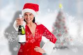 Woman holding a champagne bottle against blurry christmas tree in room poster