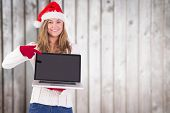 Festive blonde pointing to laptop against blurred wooden planks poster