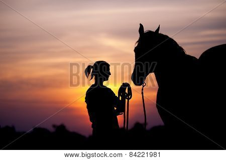 The girl near to a horse standing in front of a beautiful sunset. Silhouette of a woman and a horse.