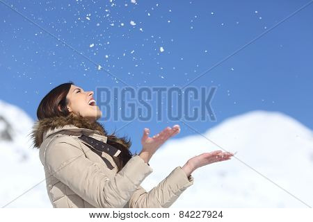 Happy Woman Throwing Snow In The Air On Winter Holdays