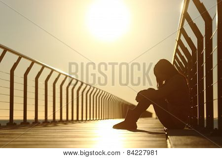 Sad teenager girl depressed sitting in the floor of a bridge on the beach at sunset poster