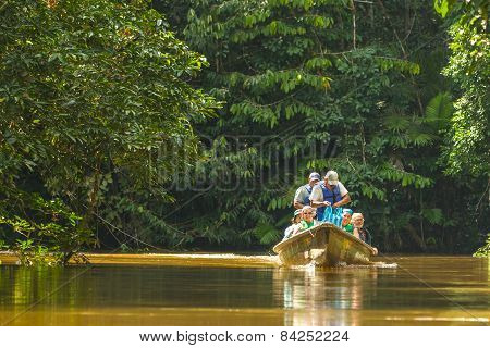 Cuyabeno, Ecuador - 20 March 2015: Happy European Biologists In The Canoe Crossing Cuyabeno River, South America In Cuyabeno On March 20, 2015