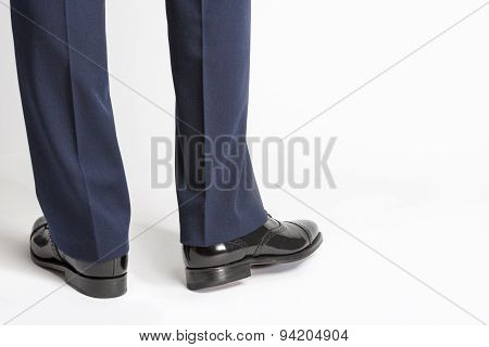 Man In Stylish Black Shiny Male Semi-brogue Posing In Reversed Position Against White.
