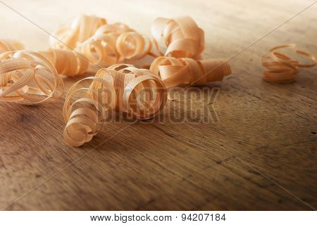 Beautiful wood shavings, on an old work desk. Shallow depth of field.