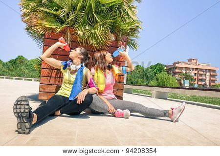 Sporty Girlfriends Drinking Energetic Juice During A Break At Run Training In Urban Park Area