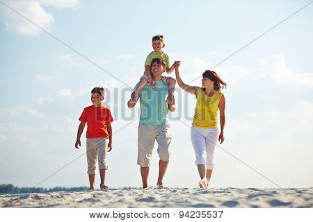 Happy family in casualwear walking on sandy beach