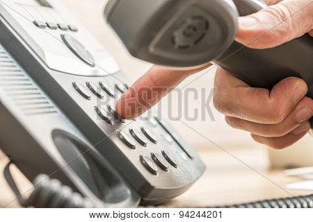 Closeup Of Male Telemarketing Salesperson Holding A Telephone Reciver Dialing Phone Number