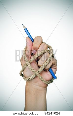 the hand of a man tied with rope, holding a pencil, depicting the idea of repression of freedom of press or freedom of expression