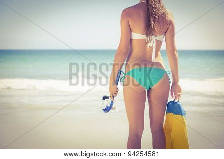 Back turned blonde holding scuba diving gear on the beach