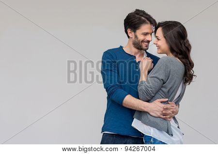 Happy couple embracing against on gray background