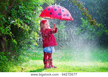 Little Girl With Umbrella Playing In The Rain